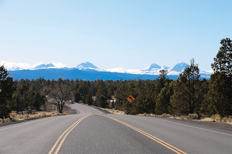 A road in Bend with coniferous trees and mountains in the background.