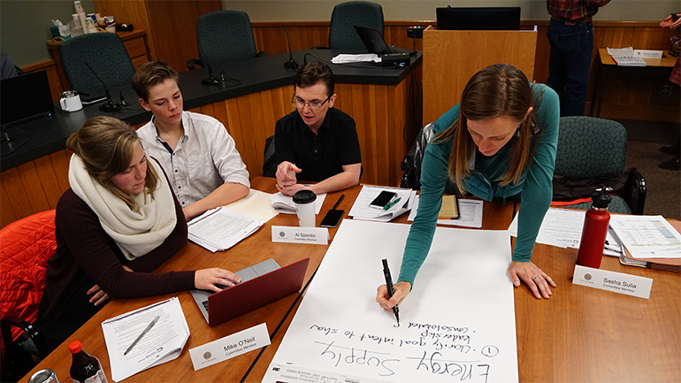 Four individuals sit around a table conversing while one takes notes on a large piece of paper.